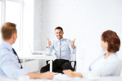 Businessman showing thumbs up in office Stock Photos