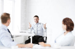 Businessman showing thumbs up in office Stock Images