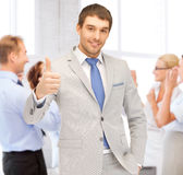 Businessman showing thumbs up in office Royalty Free Stock Photos