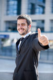 Businessman showing thumbs-up sign. Young success businessman showing thumbs-up sign, outdoor Royalty Free Stock Photo