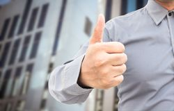 Businessman showing thumbs up sign. Standing in office Stock Image
