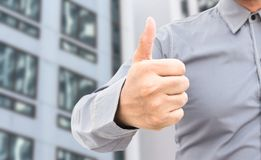 Businessman showing thumbs up sign standing in office. Businessman showing thumbs up sign standing in a office Royalty Free Stock Photos