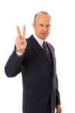 Businessman showing victory sign. Isolated on white Royalty Free Stock Image