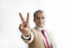 Businessman showing Victory sign with his hand gesture. Royalty Free Stock Image