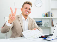 Businessman showing victory sign. Portrait of happy businessman showing victory sign in modern office Royalty Free Stock Photography