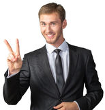 Businessman showing victory sign. Young businessman showing victory sign Stock Photography