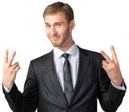 Businessman showing victory sign. Young businessman showing victory sign Stock Images