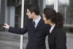 Businessman showing the way. To a woman stock images