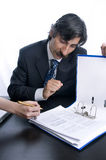 Businessman Showing a woman where to sign. The women's hands can be seen about to sign Royalty Free Stock Image