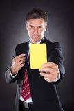 Businessman Showing Yellow Card Royalty Free Stock Photography