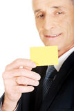 Businessman showing a yellow identity name card Royalty Free Stock Image
