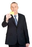 Businessman showing a yellow identity name card Stock Photo