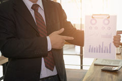 Businessman shows analytic financial accounting market chart and Stock Photos