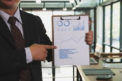 Businessman shows analytic financial accounting market chart and Royalty Free Stock Photos