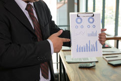 Businessman shows analytic financial accounting market chart and Royalty Free Stock Image