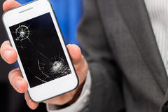 Businessman shows broken smartphone Royalty Free Stock Photos