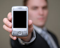 Businessman Shows Cell Phone with Shallow Depth of Field Royalty Free Stock Photos