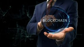 Businessman shows concept hologram Blockchain on his hand. Man in business suit with future technology screen and modern cosmic background royalty free stock photography