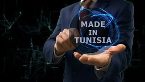 Businessman shows concept hologram Made in Tunisia on his hand. Man in business suit with future technology screen and modern cosmic background stock footage
