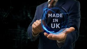 Businessman shows concept hologram Made in UK on his hand. Man in business suit with future technology screen and modern cosmic background royalty free stock images