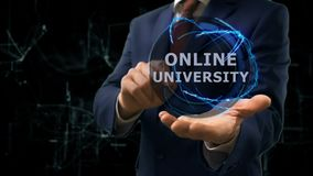 Businessman shows concept hologram Online university on his hand. Man in business suit with future technology screen and modern cosmic background stock video