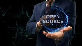 Businessman shows concept hologram Open source on his hand. Man in business suit with future technology screen and modern cosmic background Stock Images