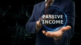 Businessman shows concept hologram Passive income on his hand. Man in business suit with future technology screen and modern cosmic background Stock Images