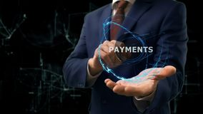 Businessman shows concept hologram Payments on his hand. Man in business suit with future technology screen and modern cosmic background Stock Photos