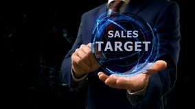 Businessman shows concept hologram Sales target on his hand. Man in business suit with future technology screen and modern cosmic background Royalty Free Stock Images