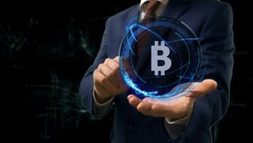 Businessman shows concept hologram Sign BTC on his hand. Man in business suit with future technology screen and modern cosmic background Stock Images