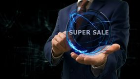 Businessman shows concept hologram Super sale on his hand. Man in business suit with future technology screen and modern cosmic background Royalty Free Stock Photography