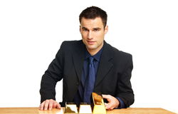 Businessman shows gold brick Stock Images