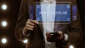 Businessman shows hologram with text Blockchain. Businessman activates conceptual HUD hologram on smartphone with text Blockchain. Man in a white shirt and stock video footage
