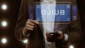 Businessman shows hologram with text Build. Businessman activates conceptual HUD hologram on smartphone with text Build. Man in a white shirt and jacket with a stock video footage
