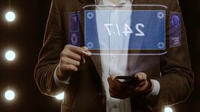 Businessman shows hologram with text 24 7. Businessman activates conceptual HUD hologram on smartphone with text 24 7. Man in a white shirt and jacket with a stock footage