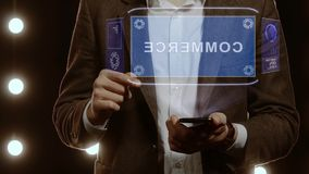 Businessman shows hologram with text Commerce. Businessman activates conceptual HUD hologram on smartphone with text Commerce. Man in a white shirt and jacket stock video
