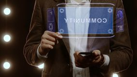 Businessman shows hologram with text Community. Businessman activates conceptual HUD hologram on smartphone with text Community. Man in a white shirt and jacket stock video