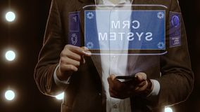 Businessman shows hologram with text CRM system. Businessman activates conceptual HUD hologram on smartphone with text CRM system. Man in a white shirt and stock video