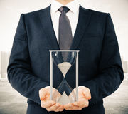 Businessman shows hourglass, time concept Royalty Free Stock Photo