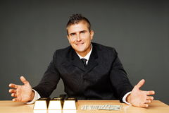 Businessman shows on money and gold brick Royalty Free Stock Image