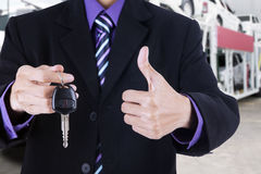 Businessman shows OK sign and a car key Royalty Free Stock Photography