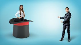 A businessman shows a self-assured businesswoman standing inside a giant illusionists hat on a blue background. Best employee. Magical accountant. Company Royalty Free Stock Images