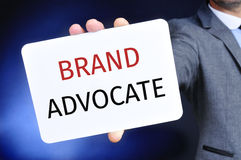 Businessman shows a signboard with the text brand advocate Royalty Free Stock Image