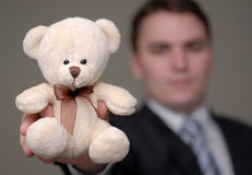 Businessman Shows Teddy Bear with Shallow Depth of Field. Young businessman holding teddy bear towards the camera. Shallow depth of field stock photos