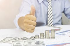 Businessman shows thumb with coins and business paper on work table, concept as success in finance, growth. Ans walk step by step royalty free stock photo