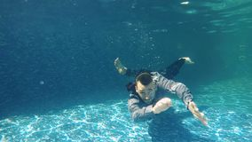 Businessman shows thumbs up under water. Underwater. Businessman in suit dives under water in blue swimming pool. The guy in suit creates air bubbles around him stock video