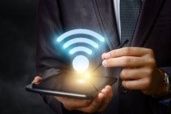 Businessman shows a WiFi symbol . Businessman shows a WiFi symbol on the tablet Royalty Free Stock Photo