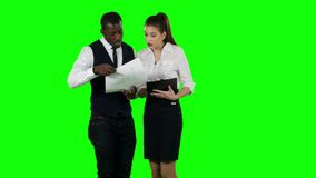 Businessman shows a woman new information. Green screen. Businessman shows a woman new information, serious working moments, a large number of documents, working stock video
