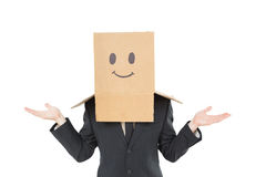 Businessman shrugging with box on head Stock Image