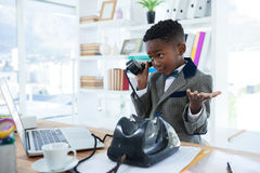 Businessman shrugging while talking on telephone. At office desk Royalty Free Stock Photography